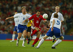 Wales' Ryan Giggs and Finland's Teemu Tainio during the Euro 2004 qualifying match at the Milennium Stadium. (Pic by David Rawcliffe/Propaganda)