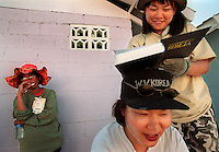 World Vision s Chacky Nakashima from Japan uses  Sarah Soon-Young  s (from Korea) head as a desk to sign a bible these volunteers will present to home-owner Salome Caspillo. Nena Malimban a friend of Salome s and a local volunteer looks on.(Janet Jensen/The News Tribune)