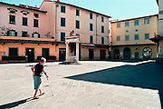 Italie, Toscane, 25-8 2001Oudere vrouw loopt op een pleintje in een stadje.Elderly woman walks on a little square in a small town.Foto: Flip Franssen