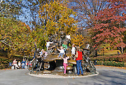 Children climb on the Alice in Wonderland Statue in Central Park, New York City in Autumn.