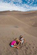 View of Great Sand Dunes National Monument and Preserve, near Alamosa, Colorado, USA; with boy and girl