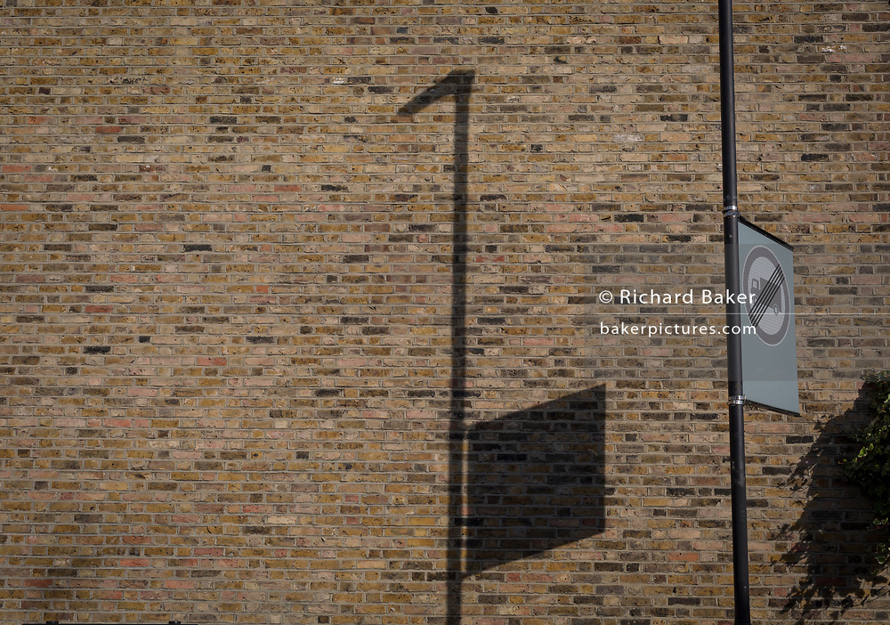 The shadow of a nearby lamp post and square traffic sign on the brick wall of an end terraced home, on 3rd July 2017, in Herne Hill, London, England.