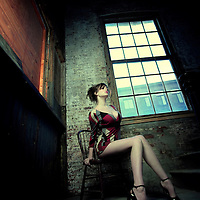 A young woman posing on a wooden chair in an old building