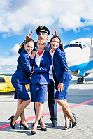 Portrait of three young attractive flight attendants standing with mature pilot against airplane in airport
