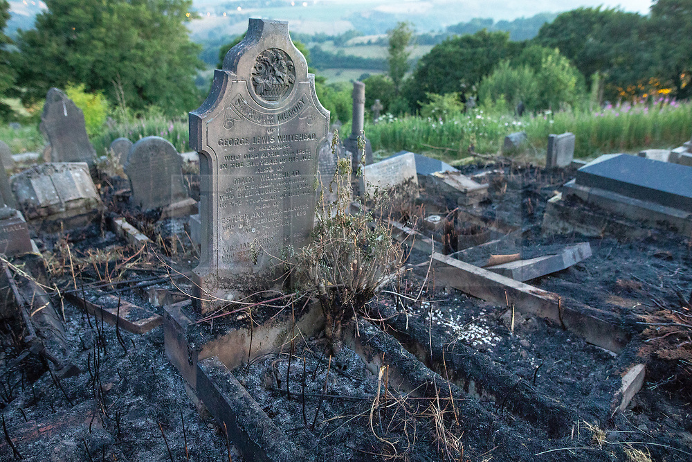 """© Licensed to London News Pictures . 28/06/2018 . Saddleworth , UK . Scorched earth in Saddleworth Graveyard where fire burned through dry grass in the late hours of Wednesday 27th June (yesterday) and had to be extinguished by firefighters . The army are being called in to support fire-fighters , who continue to work to contain large wildfires spreading across Saddleworth Moor and affecting people across Manchester and surrounding towns . Very high temperatures , winds and dry peat are hampering efforts to contain the fire , described as """" unprecedented """" by police and reported to be the largest in living memory . Photo credit: Joel Goodman/LNP"""