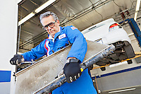 Portrait of mechanic working on an auto part