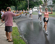 A female runner get cooled off the the spray from a spectator's hose during the 25th annual Orange Classic 10K road race in Middletown, N.Y., on June 11, 2005. The weather for the race was hot and humid.