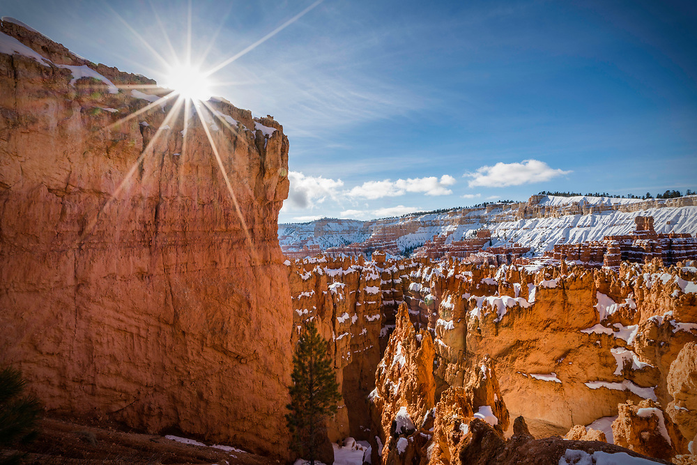 The sun crests over a sandstone hoodoo in the Wall Street section of Bryce Canyon National Park off from the Navajo Loop trail at Sunset Point in Winter.