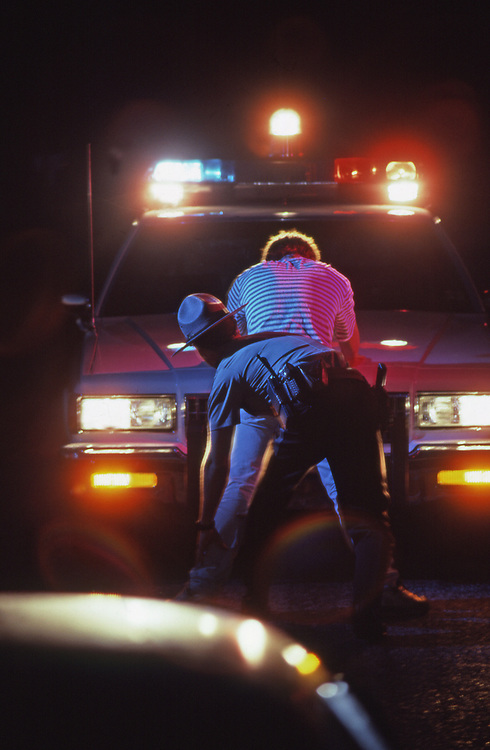 Police frisk young man at road stop