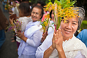 "15 JULY 2011 - PHRA PHUTTHABAT, SARABURI, THAILAND: A woman prepares to offer flowers to the monks during the Tak Bat Dok Mai at Wat Phra Phutthabat in Saraburi province of Thailand, Friday, July 15. Wat Phra Phutthabat in Phra Phutthabat, Saraburi, Thailand, is famous for the way it marks the beginning of Vassa, the three-month annual retreat observed by Theravada monks and nuns. The temple is highly revered in Thailand because it houses a footstep of the Buddha. On the first day of Vassa (or Buddhist Lent) people come to the temple to ""make merit"" and present the monks there with dancing lady ginger flowers, which only bloom in the weeks leading up Vassa. They also present monks with candles and wash their feet. During Vassa, monks and nuns remain inside monasteries and temple grounds, devoting their time to intensive meditation and study. Laypeople support the monastic sangha by bringing food, candles and other offerings to temples. Laypeople also often observe Vassa by giving up something, such as smoking or eating meat. For this reason, westerners sometimes call Vassa the ""Buddhist Lent."" The tradition of Vassa began during the life of the Buddha. Most of the time, the first Buddhist monks who followed the Buddha did not stay in one place, but walked from village to village to teach. They begged for their food and often slept outdoors, sheltered only by trees. But during India's summer rainy season living as homeless ascetics became difficult. So, groups of monks would find a place to stay together until the rain stopped, forming a temporary community. Wealthy laypeople sometimes sheltered monks on their estates. Eventually a few of these patrons built permanent houses for monks, which amounted to an early form of monastery.    PHOTO BY JACK KURTZ"