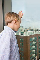 Boy looking out through window at home