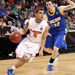 Mar 17, 2011; Tampa, FL, USA; Florida Gators guard Scottie Wilbekin (5) drives past UC Santa Barbara Gauchos forward Jon Pastorek (32) during first half of the second round of the 2011 NCAA men's basketball tournament at the St. Pete Times Forum.  Mandatory Credit: Derick E. Hingle