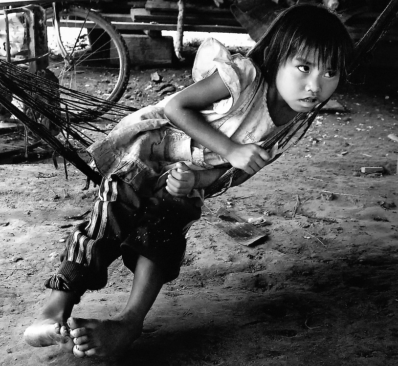 A girls relaxes in the cool in a village in Savannakhet, Laos.