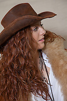 Beautiful teenager with cowboy hat and fur looking away