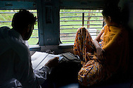 Train passengers on the Himsagar Express 6318 as it passes through the border of Madhya Pradesh to Maharashtra on 8th July 2009.. .6318 / Himsagar Express, India's longest single train journey, spanning 3720 kms, going from the mountains (Hima) to the seas (Sagar), from Jammu and Kashmir state of the Indian Himalayas to Kanyakumari, which is the southern most tip of India...Photo by Suzanne Lee / for The National