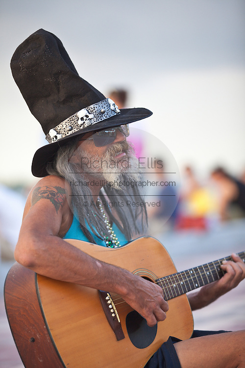 A busker plays guitar along the Mallory Square dock in Key West, Florida.