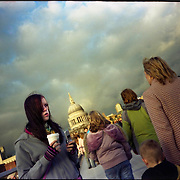 A girl drinks coffe as she holds her mobile telephone at the Millenium bridge, close to Saint Paul's cathedral in London.