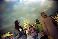A girl drinks coffe as she holds her mobile telephone at the Millennium bridge, close to Saint Paul's cathedral in London.