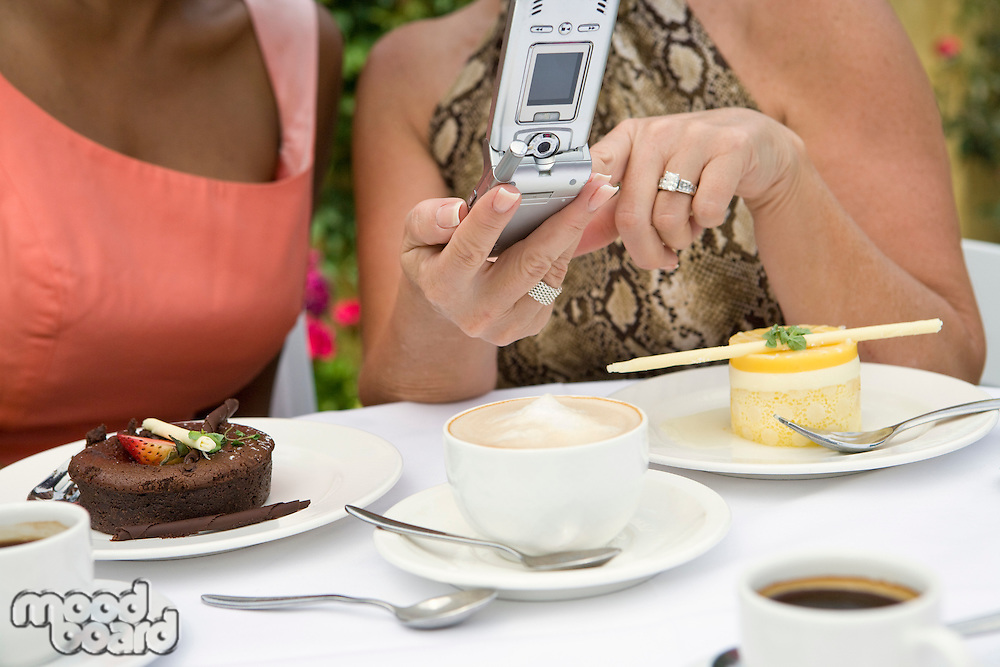 Women using mobile phone by dessert on table