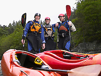 Three men with kayaks by river portrait