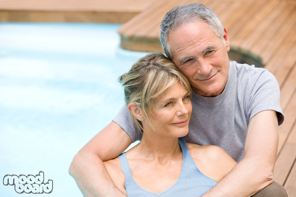 Middle-aged couple sitting embracing by swimming pool portrait