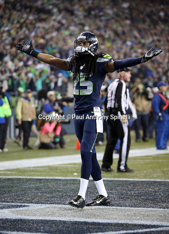 Seattle Seahawks cornerback Richard Sherman (25) stretches his arms wide as he celebrates after Seattle Seahawks free safety Earl Thomas (29) intercepts a late second quarter pass during the NFL week 19 NFC Divisional Playoff football game against the Carolina Panthers on Saturday, Jan. 10, 2015 in Seattle. The Seahawks won the game 31-17. ©Paul Anthony Spinelli
