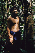 Baru, a semi-nomadic Penan, indigenous hunter-gatherer, searching for sago and wild boar. Dressed in traditional 'chawats' loincloth, searching for sago from the forest. In the rainforest near Long Tegang, Limbang district, Sarawak, Borneo 1989<br /> <br /> Tropical rainforest and one of the world's richest, oldest eco-systems, flora and fauna, under threat from development, logging and deforestation. Home to indigenous Dayak native tribal peoples, farming by slash and burn cultivation, fishing and hunting wild boar. Home to the Penan, traditional nomadic hunter-gatherers, of whom only one thousand survive, eating roots, and hunting wild animals with blowpipes. Animists, Christians, they still practice traditional medicine from herbs and plants. Native people have mounted protests and blockades against logging concessions, many have been arrested and imprisoned.