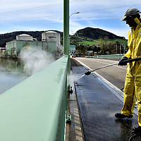 Employee cleaning the bridge leading to Beznau Nuclear Power Station situated on an articficial island in the Aar River, its two reactors /Beznau I and Beznau II) started work in 1969 and 1972. The plant is located close to the German border.<br />