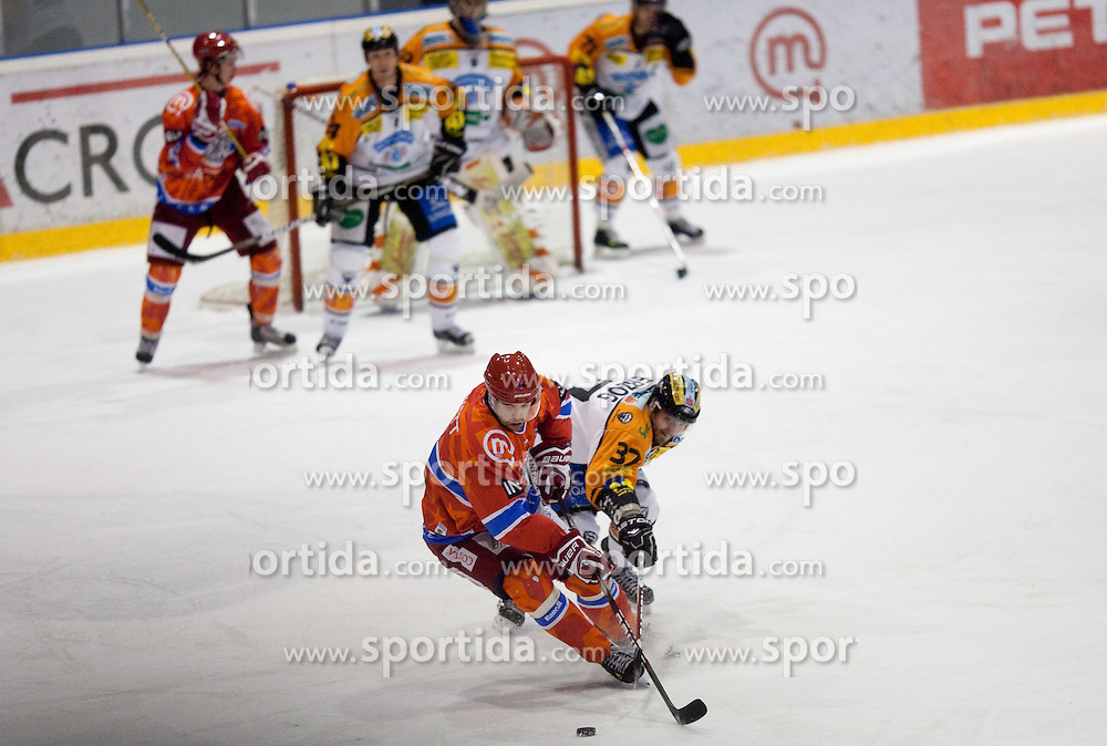 Jason Beckett of Tilia Olimpija vs Stefan Herzog of Graz during ice hockey match between HK Acroni Jesenice and  Moser Medical Graz 99ers in 24th Round of EBEL league, on December 3, 2010 in Arena Podmezakla, Jesenice, Slovenia.  (Photo By Vid Ponikvar / Sportida.com)