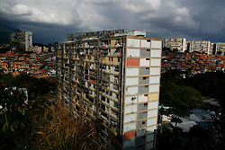 "A building in the 23 de Enero barrio in Caracas.  This building, along with 37 others, was constructed by General Marcos Perez Jimenez who organized a coup in 1952 and later installed himself as president of Venezuela. Jimenez named the barrio ""December 2""  after the date which he staged the military coup. Years later, residents renamed the barrio ""23 de Enero"" (23 January) for the day Jimenez was overthrown in 1958."