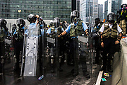 Riot police drink water as they face off with protesters near the Central Government Offices, during a protest against a proposed extradition law in Hong Kong, SAR China, on Wednesday, June 12, 2019. Hong Kong's legislative chief postponed the debate on legislation that would allow extraditions to China after thousands of protesters converged outside the chamber demanding the government to withdraw the bill. Photo by Suzanne Lee/PANOS