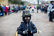 UNITED KINGDOM, Whittlesey: Straw Bear Festival. Hedley Fisher, aged 5 and a fan of The Witchmen Morris dancers, stands among the crowds to watch The Witchmen perform at the Straw Bear festival this weekend. The Witchmen paint their faces black and have a large feather protruding from a black hat.  A number of theories for the black face paint exist, from Moorish mimicry to a form of disguise. The three day festival, which originated in 1882, consists of traditional Molly, Morris, Clog and Sword dancing as well as parading a large straw character known as 'The Bear' through the town. Rick Findler  / Story Picture Agency