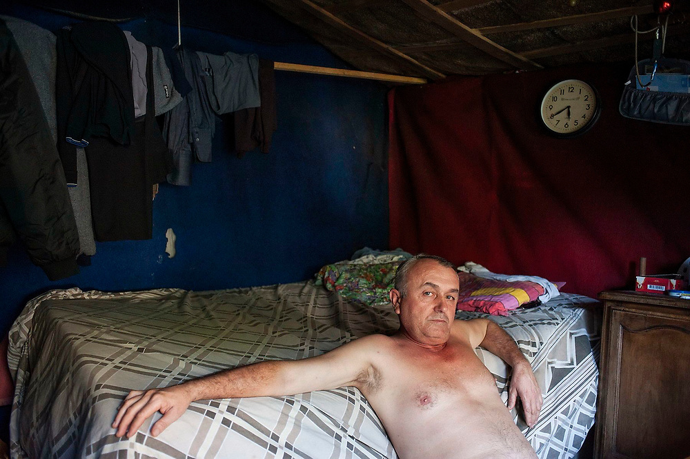 Ion Pop from Tarsolt in Maramures in Romania sits in his makeshift shelter in a forest on the outskirts of Paris. This settlement has been built by a group of around 80 people from Calinesti Oas who have built huts out of materials they have been able to find and have been living here since 2002. Some of them have not found work in France and therefore can't afford to pay rent. Others prefer to live in these makeshift settlements to save money. Ion is planning to return to Romania since he wasn't able to find any work.