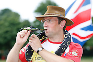 Photo by Andrew Tobin/Tobinators Ltd - 07710 761829 - Jim Collins shoots his hi tech laser sighted peas shooter complete with anaconda during the World Peashooting Championships held at Witcham, Cambridgeshire, UK on 13th July 2013. Run in conjunction with the village fair, the Championships have been held in Witcham since 1971 when they were started by a Mr Tyson, the village schoolmaster, in order to raise funds for the village hall.Competitors come from as far afield as the USA and New Zealand to attempt to win the event. The latest technology is often used, including laser sights and titanium and carbon fibre peashooters. All peashooters must conform to strict length rules, not exceeding 12 inches, and have to hit a target 12 feet away. Shooting 5 peas at a plasticine target attached to a hay bale, the highest scorers move through the initial rounds to a knockout competition, followed by a sudden death 10-pea shootout.