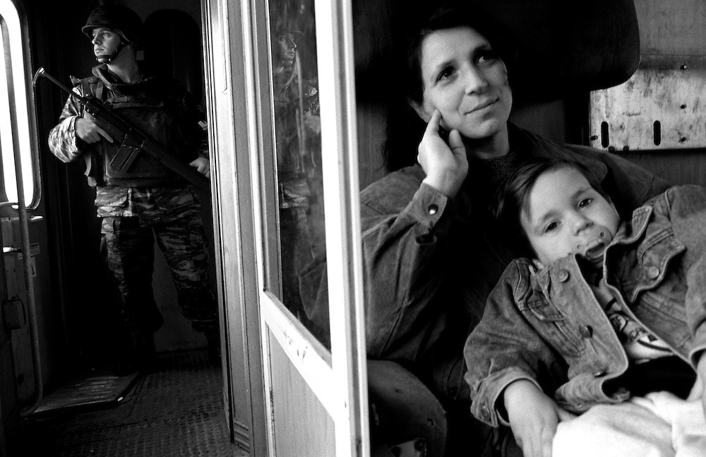 """Neon and his mother on the safe train. Greek Kfor (Kosovo force) runs the train the """"Serb"""" train - from the North of Kosovo to the South. The Serbs and the Roma, who still live in Kosovo, are totally isolated in enclaves. After several deadly attacks by Albanian extremists, they are too scared too use the roads. The train is a safe way to travel."""