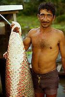 April 1986, Amazon River, Brazil --- Local Man Holds Giant Amazon Pirarucu --- Image by © Owen Franken/CORBIS