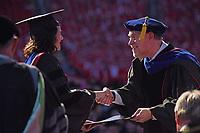 Interim grad school dean Peter Harries (right) congratulates a graduate.