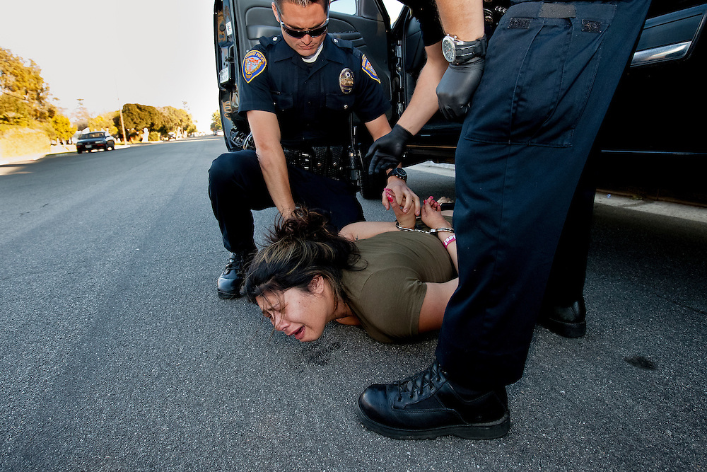 After being combative and resisting arrest, Vanessa Franco is placed on the ground and handcuffed. Dec. 7, 2011. Oxnard, Calif. Her charges included driving under the influence of alcohol or drugs, hit and run, resisting arrest and driving without a license. (Photo by Gabriel Romero ©2011)