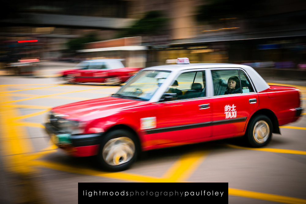 Rushing Hong Kong taxi with woman in rear seat