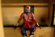 SRI LANKA...Udappuwa festival. Participants at the festival, a ceremony that leaves from the Sri Kali Amman Hindu kovil in the afternoon, early evening. This man sits on a wall in the temple, while others in the procession are dressed in costume and have their make up applied.They will go to the main Vishnu kovil in the north of the village.