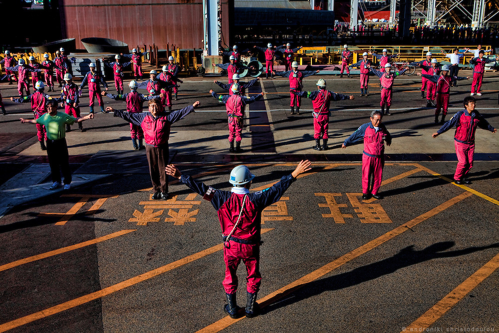 Every morning the workers practise 10 minutes exercises before they start working at Tsuneishi shipbuilding company.