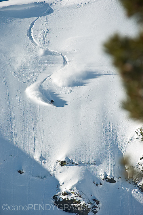 profesional snowboarder Dave Downing makes perfect turns down a steep face in the Tahoe Backcountry