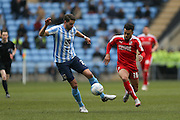 Coventry City defender Aaron Martin (21) wins the ball from Swindon Town forward Nicky Ajose (10)  during the Sky Bet League 1 match between Coventry City and Swindon Town at the Ricoh Arena, Coventry, England on 19 March 2016. Photo by Simon Davies.