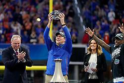 Florida Gators head coach Dan Mullen holds up the Peach Bowl Trophy after winning the Chick-fil-A Peach Bowl, Saturday, December 29, 2018, in Atlanta. ( Paul Abell via Abell Images for Chick-fil-A Peach Bowl)