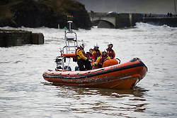 © Licensed to London News Pictures. 04/01/2014. Aberystwyth, UK Just after 10am on Saturday 4 Jan 2014 the RNLI inshore rescue team were called out to rescue a young man (EDWARD LAXTON, a 21 year old first year student at Aberystwyth university), when he was spotted photographing in a dangerous position art the extreme end of the harbour jetty at the height of the storm. Picture shows the man on the jetty prior to the rescue. Photo credit : Keith Morris/LNP