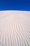 Morning light on dune patterns in gypsum sand under blue sky, White Sands National Monument, New Mexico
