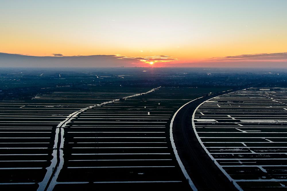 Nederland, Zuid-Holland, Krimpen aan de IJssel, 07-02-2018; verkaveling in tegenlicht in de  Krimpenerwaard bij zonsondergang. Skyline Rotterdam aan de verre horizon.<br /> Polder in backlight at sunset, skyline Rotterdam in the far distance.<br /> luchtfoto (toeslag op standard tarieven);<br /> aerial photo (additional fee required);<br /> copyright foto/photo Siebe Swart