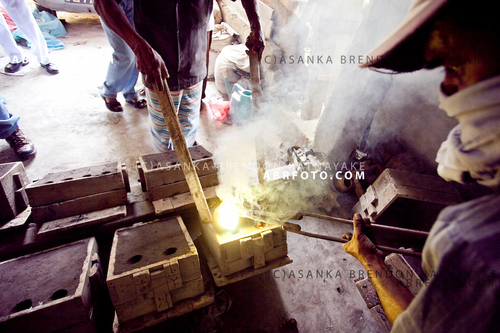 Brass craftsman pours hot melted molten brass into the mould used to shape brass lamps & lanterns.
