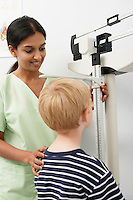 Young female nurse measuring boy's height