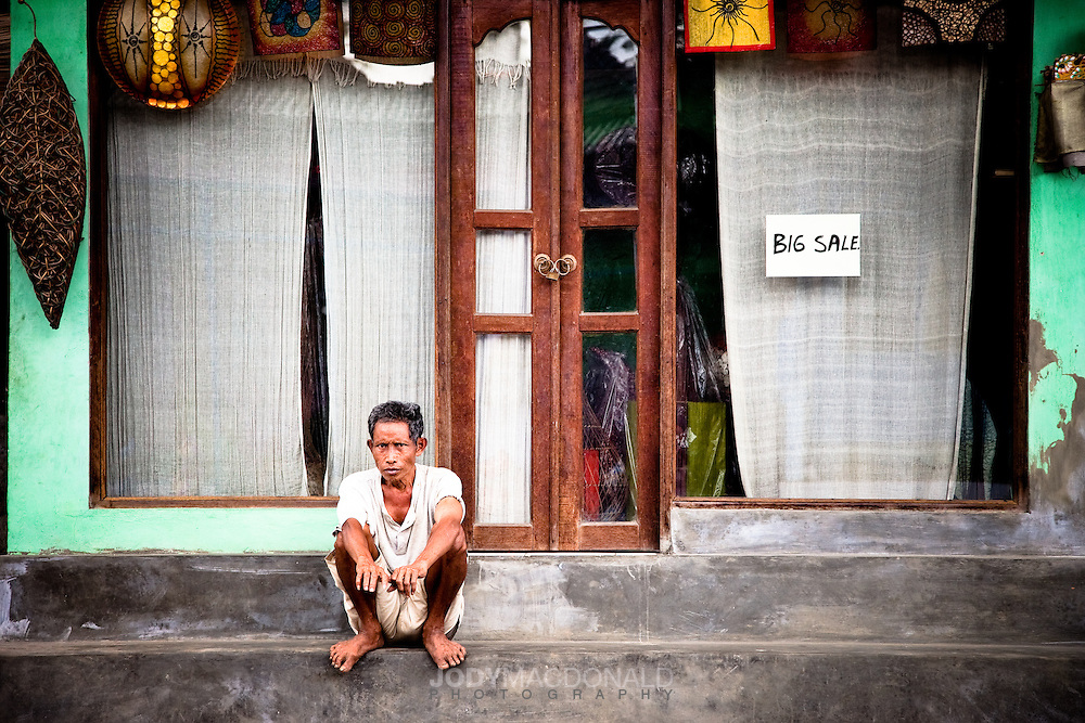 """Man sits on a sidewalk with bare feet in front of a small shop in Bali, Indonesia.  The shop announces a """"Big Sale"""" with a small simple sign hung in the window."""